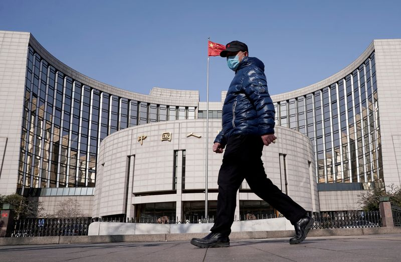 FILE PHOTO: Man wearing a mask walks past the headquarters of the People's Bank of China, the central bank, in Beijing