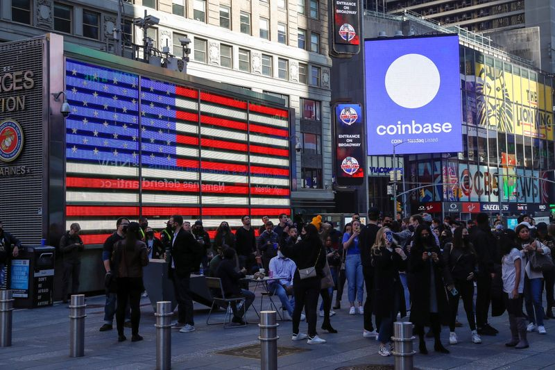 Employees of Coinbase Global Inc, the biggest U.S. cryptocurrency exchange, watch as their listing is displayed on the Nasdaq MarketSite jumbotron at Times Square in New York
