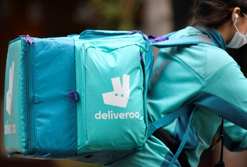 A Deliveroo delivery rider cycles in London
