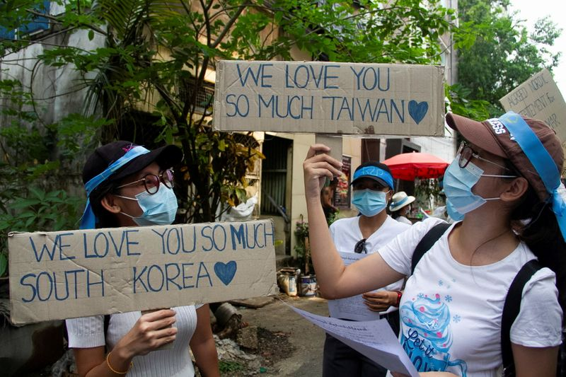 FILE PHOTO: Demonstrators carry placards as they march during a protest against military coup, in Yangon
