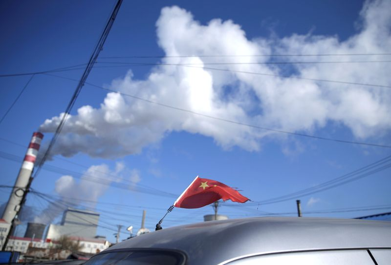 FILE PHOTO: A Chinese flag is seen on the top of a car near a coal-fired power plant in Harbin