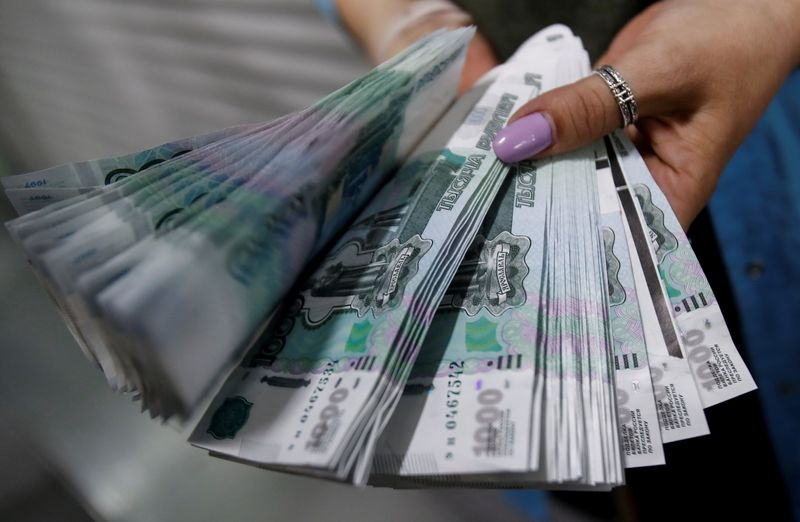 FILE PHOTO: An employee holds 1,000 Russian rouble notes at Goznak printing factory in Moscow