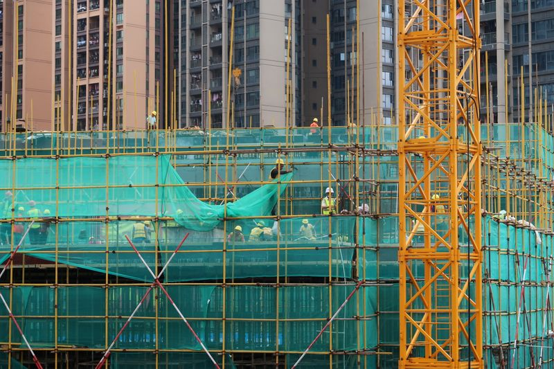 FILE PHOTO: Workers are seen on scaffoldings of a construction site near residential buildings in Shenzhen, following the novel coronavirus disease (COVID-19) outbreak