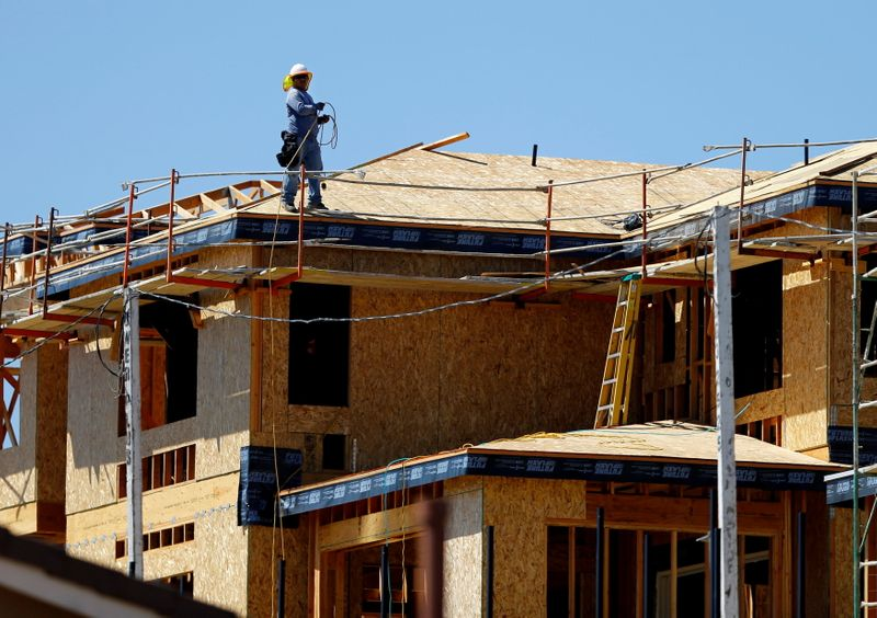 FILE PHOTO: A worker walks on the roof of a new home under construction in Carlsbad