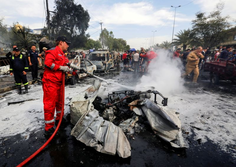 FILE PHOTO: A firefighter inspects the site of a car bomb attack in Sadr City district of Baghdad