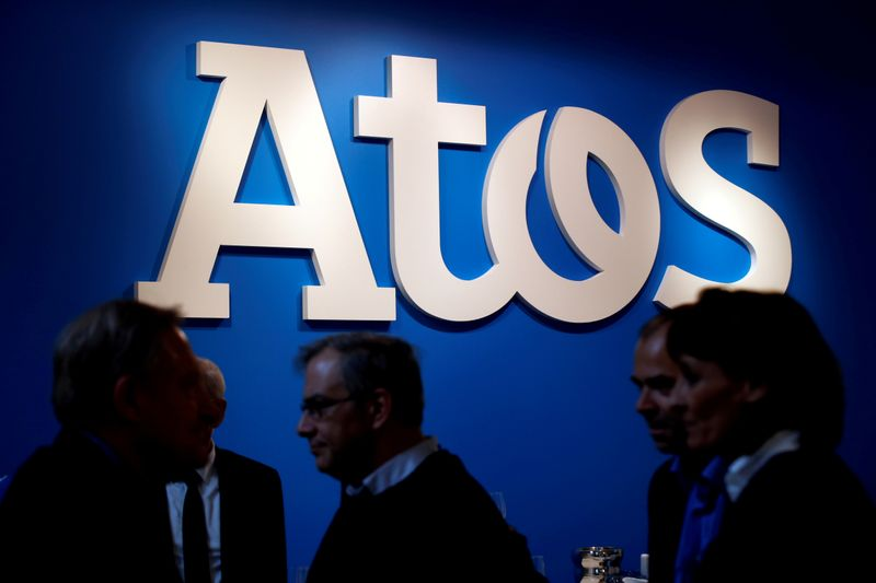 FILE PHOTO: FILE PHOTO: People walk in front of the Atos company's logo during a presentation of the new Bull sequana supercomputer in Paris