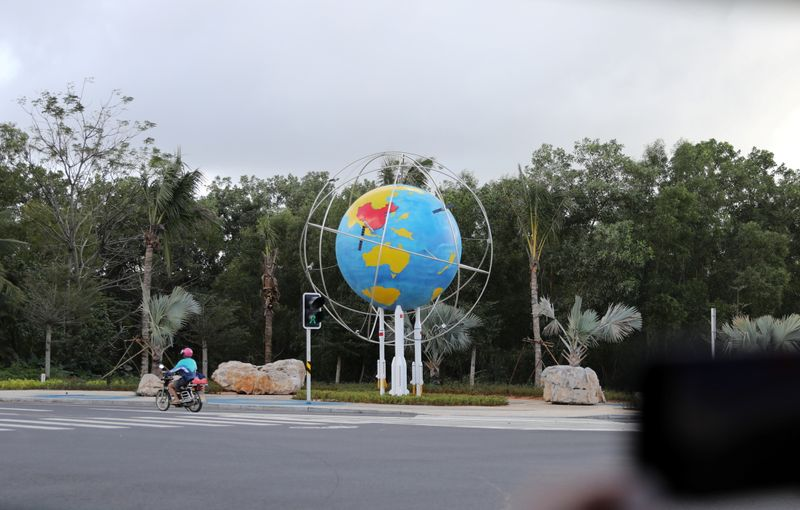 A motorcyclist passes a model of Planet Earth at a space science museum in Wenchang, Hainan