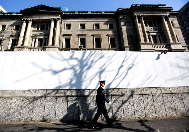 FILE PHOTO: FILE PHOTO: A security guard walks past in front of the Bank of Japan headquarters in Tokyo
