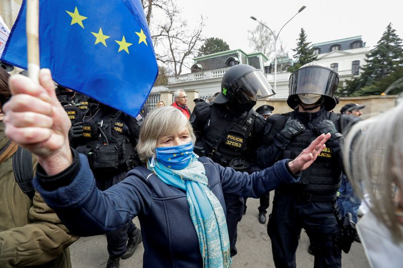 FILE PHOTO: A woman holds an EU flag next to police officers during a protest over the Russian intelligence services alleged involvement in an ammunition depot explosion in Vrbetice area in 2014, outside the Russian Embassy in Prague