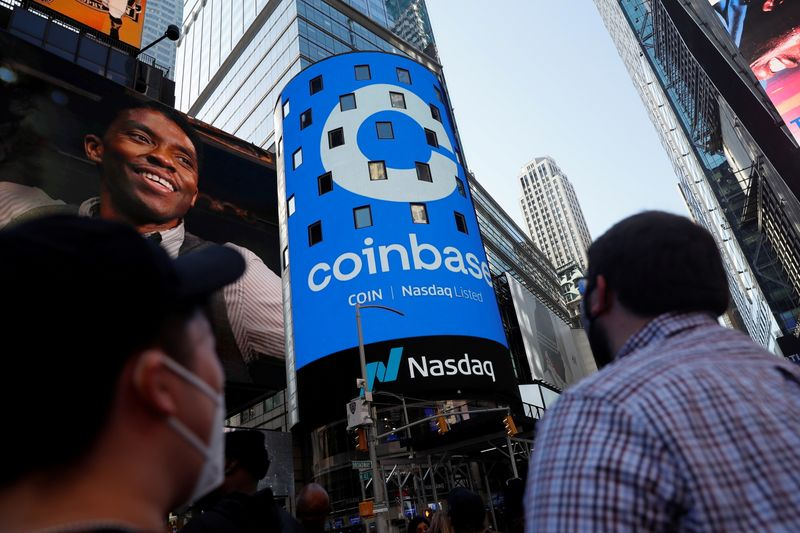 FILE PHOTO: People watch as the logo for Coinbase Global Inc, the biggest U.S. cryptocurrency exchange, is displayed on the Nasdaq MarketSite jumbotron at Times Square in New York