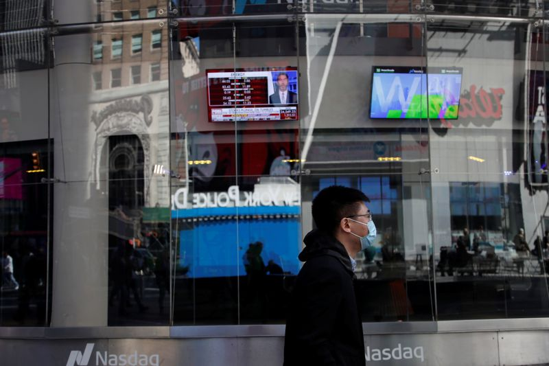A man with a face mask walks by television screens outside the Nasdaq Market Site, after further cases of coronavirus were confirmed in New York, at Times Square in New York