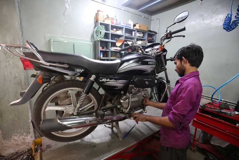 An employee works on a motorbike inside a Hero MotoCorp service station in Ahmedabad