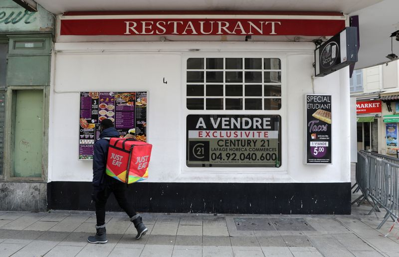 A Just Eat delivery man stands in front of a closed restaurant on sale in Nice