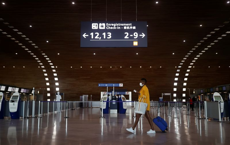 FILE PHOTO: A woman makes her way in the departures area of the Terminal 2E at Charles-de-Gaulle airport in Roissy