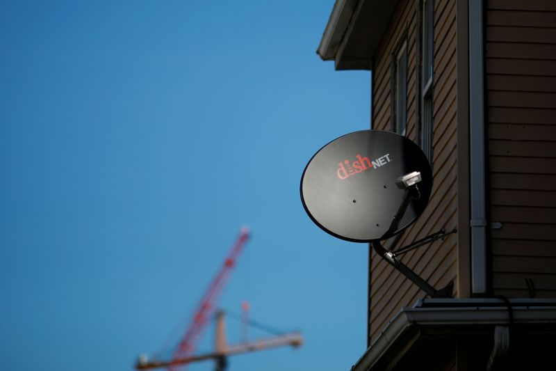 FILE PHOTO: A Dish Network receiver hangs on a house in Somerville