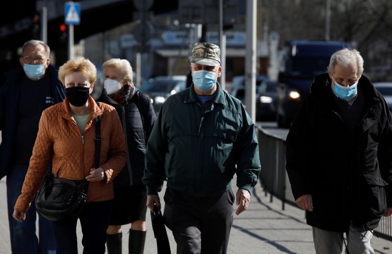 FILE PHOTO: People wearing protective masks walk in Warsaw