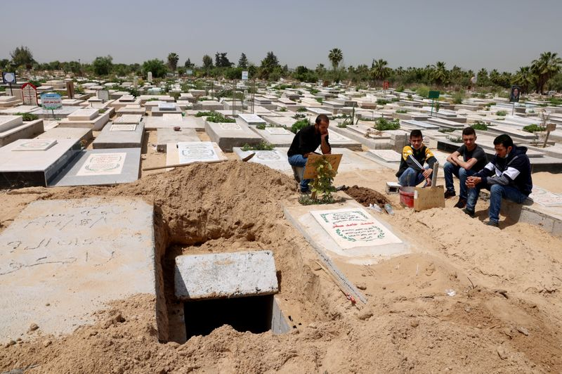 Palestinians wait to bury the body of their relative, who died after contracting COVID-19, at a cemetery, east of Gaza City
