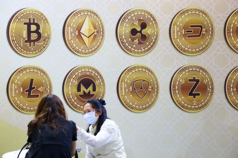 FILE PHOTO: Customers talk against a backboard with signs of cryptocurrency during 2020 Taipei International Finance Expo in Taipei,
