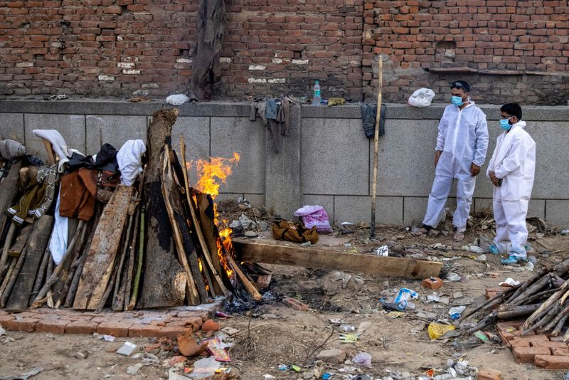 Relatives stand next to the burning funeral pyre of a person, who died due to the coronavirus disease (COVID-19), at a crematorium ground in New Delhi