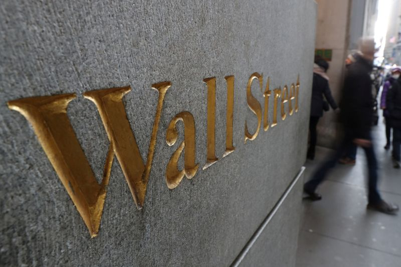 FILE PHOTO: A street sign, Wall Street, is seen outside New York Stock Exchange (NYSE) in New York City, New York