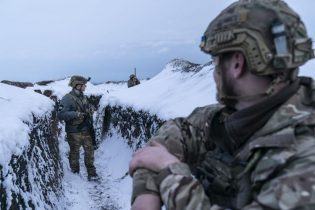 Ukrainian servicemen walk along a snow covered trench guarding their position at the frontline near Vodiane, about 750 kilometers (468 miles) south-east of Kyiv, eastern Ukraine, Saturday, March 5, 2021. The country designated 14,000 doses of its first vaccine shipment for the military, especially those fighting Russia-backed separatists in the east. Ukrainians are becoming increasingly opposed to vaccination: an opinion poll this month by the Kyiv International Institute of Sociology found 60% of the country's people don't want to get vaccinated, up from 40% a month earlier. (AP Photo/Evgeniy Maloletka)