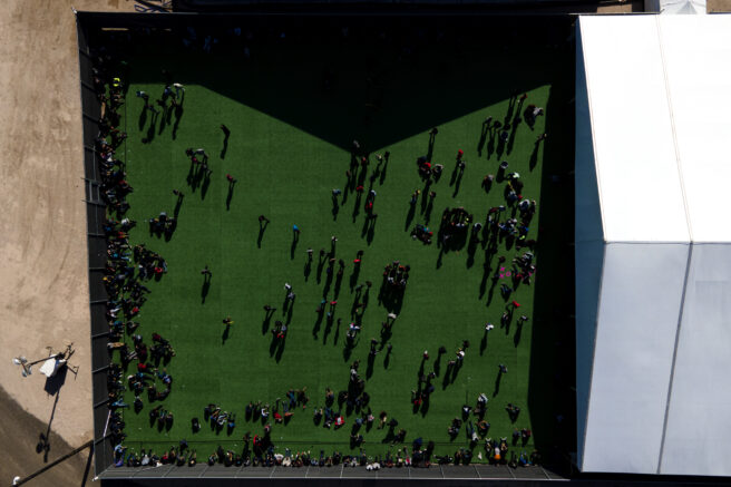 Migrants are seen in a green area outside of a soft-sided detention center after they were taken into custody while trying to sneak into the U.S., Friday, March 19, 2021, in Donna, Texas. (AP Photo/Julio Cortez)