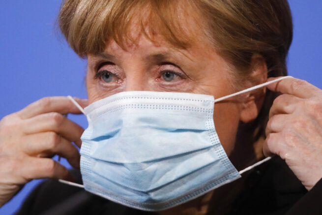 FILE-In this March 30, 2021 taken photo German Chancellor Angela Merkel puts on her face mask after she briefs the media following a virtual meeting with federal state governors at the chancellery in Berlin, Germany. Chancellor Angela Merkel has urged Germans to accept nationwide pandemic restrictions that came into force at midnight, resulting in nighttime curfews, further limits on personal contacts and access to non-essential stores in regions with high infection rates. (AP Photo/Markus Schreiber)