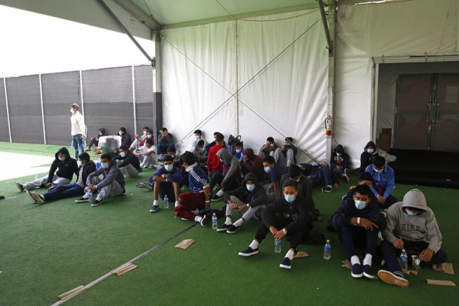 Minor children who tested positive for COVID-19 sit in the ground at the Donna Department of Homeland Security holding facility, the main detention center for unaccompanied children in the Rio Grande Valley run by U.S. Customs and Border Protection (CBP), in Donna, Texas, Tuesday, March 30, 2021. The Biden administration on Tuesday for the first time allowed journalists inside its main detention facility at the border for migrant children, revealing a severely overcrowded tent structure where more than 4,000 kids and families were crammed into pods and the youngest kept in a large play pen with mats on the floor for sleeping.(AP Photo/Dario Lopez-Mills, Pool)