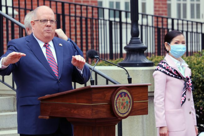 FILE - In this Monday, April 20, 2020 file photo, Maryland Gov. Larry Hogan speaks at a news conference in Annapolis, Md., with his wife, Yumi Hogan, right, where the governor announced Maryland has received a shipment from a South Korean company to boost the state's ability to conduct tests for COVID-19 by 500,000. Maryland auditors have found Gov. Larry Hogan's administration failed to follow state procurement regulations when it bought 500,000 COVID-19 tests from a South Korean company last year. The audit released Friday, April 2, 2021 also said the first batch of tests that later had to be replaced at additional $2.5 million cost had not been authorized by the U.S. Food and Drug Administration. (AP Photo/Brian Witte, File)