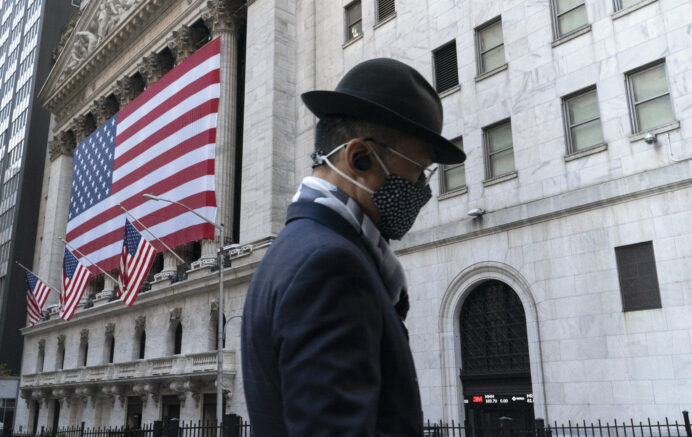 FILE - In this Nov. 16, 2020 file photo a man wearing a mask passes the New York Stock Exchange in New York. Stocks are wavering in early trading on Wall Street, holding the market near record highs it set earlier in the week. The S&P 500 edged up 0.1% early Wednesday, April 7, 2021, and the Dow Jones Industrial Average climbed 0.2%. (AP Photo/Mark Lennihan, File)