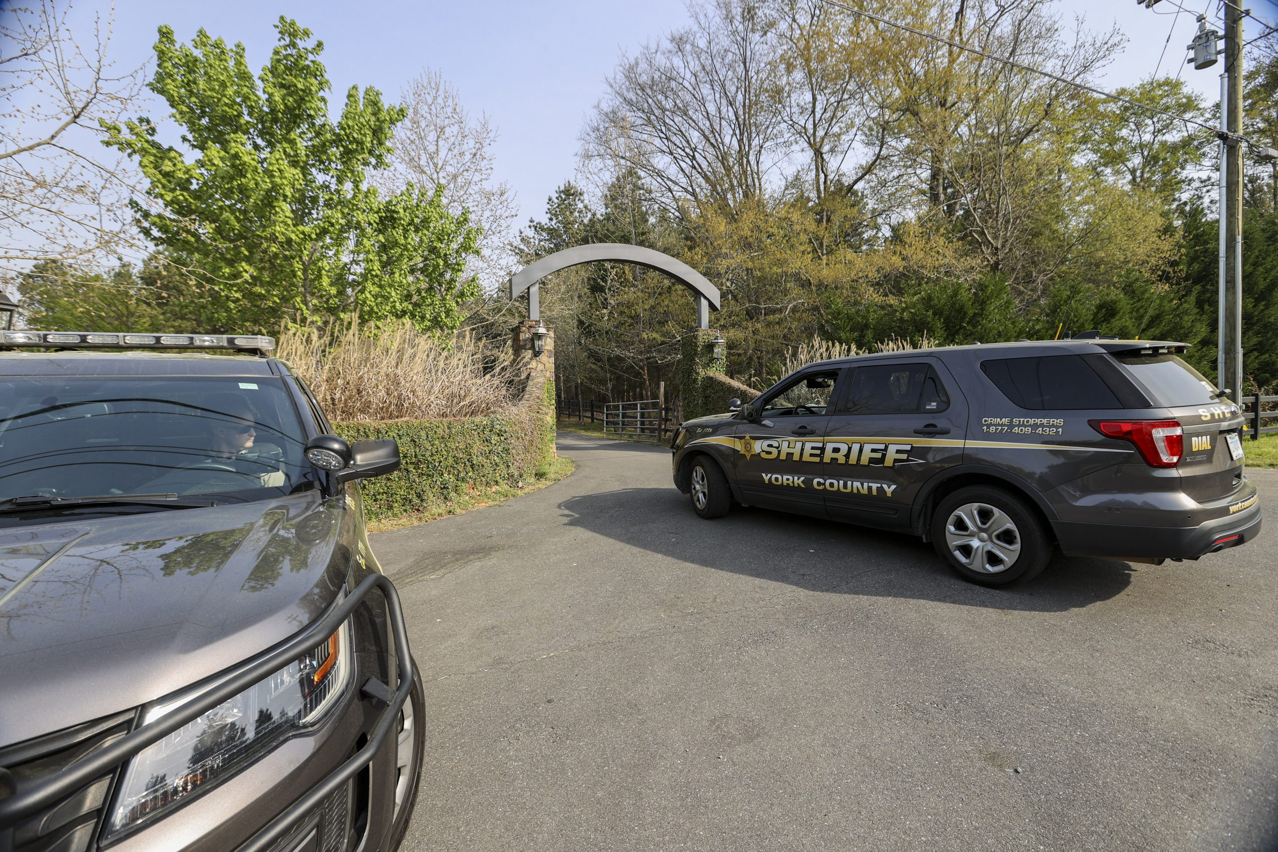 A York County sheriff vehicle drives onto the property where multiple people, including a prominent doctor, were fatally shot a day earlier, Thursday, April 8, 2021, in Rock Hill, S.C. A source briefed on the mass killing said the gunman was former NFL player Phillip Adams, who shot himself to death early Thursday. (AP Photo/Nell Redmond)