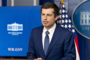 Transportation Secretary Pete Buttigieg takes a question from a reporter at a press briefing at the White House, Friday, April 9, 2021, in Washington. (AP Photo/Andrew Harnik)