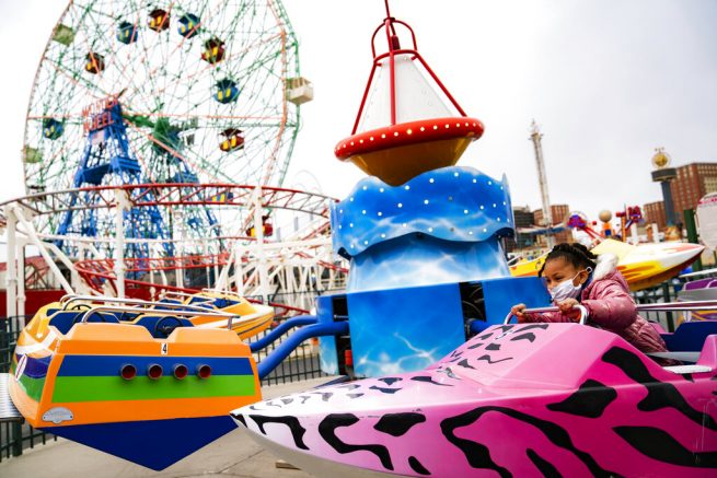 A child enjoys a ride after the seasonal opening of the Coney Island amusement park area, Friday, April 9, 2021, in the Brooklyn borough of New York. Coney Island's illustrious amusement parks are reopening Friday after the coronavirus pandemic shuttered them all last year. (AP Photo/John Minchillo)