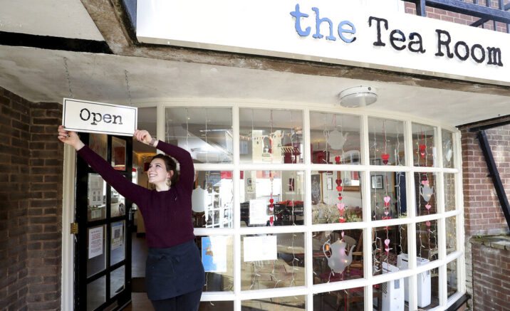 Harriet Henry, manager of The Tea Room in Knutsford, England, poses with the Open sign outside her cafe, as she prepares to open, Sunday April 11, 2021. Millions of people in Britain will get their first chance in months for haircuts, casual shopping and restaurant meals on Monday, as the government takes the next step on its lockdown-lifting roadmap. (Martin Rickett/PA via AP)