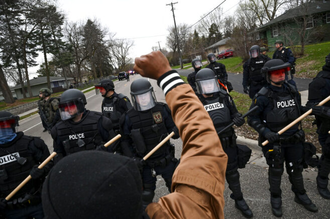 A man raises his fist in the air as he yells at police donning riot gear at 63rd and Lee Avenues North, Sunday, April 11, 2021, in Brooklyn Center, Minn. The family of Daunte Wright, 20, told a crowd that he was shot by police Sunday before getting back into his car and driving away, then crashing the vehicle several blocks away. The family said Wright was later pronounced dead. (Aaron Lavinsky/Star Tribune via AP)