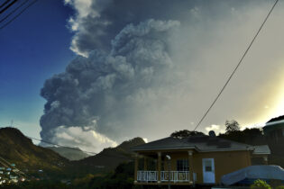 Ash rises into the air as La Soufriere volcano erupts on the eastern Caribbean island of St. Vincent, Tuesday, April 13, 2021. (AP Photo/Orvil Samuel)