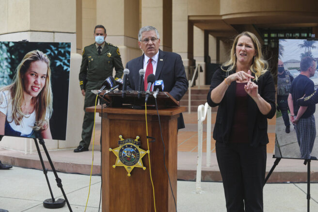 Cal Poly President Jeffrey Armstrong, center, speaks during a press conference Tuesday, April 13, 2021, San Luis Obispo, Calif. At left is a photo of Kristin Smart. Smart, 19, of Stockton, California, vanished in May 1996 while returning to a dorm at California Polytechnic State University, San Luis Obispo, after a party. San Luis Obispo County Sheriff Ian Parkinson stands in the background and interpreter Robin Babb is at right. (David Middlecamp/The Tribune (of San Luis Obispo) via AP)