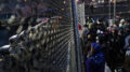 Authorities guard a perimeter fence as demonstrators gather on the other side Tuesday, April 13, 2021, outside the Brooklyn Center (Minn.) Police Department during a protest over Sunday's shooting death of Daunte Wright during a traffic stop. (AP Photo/John Minchillo)