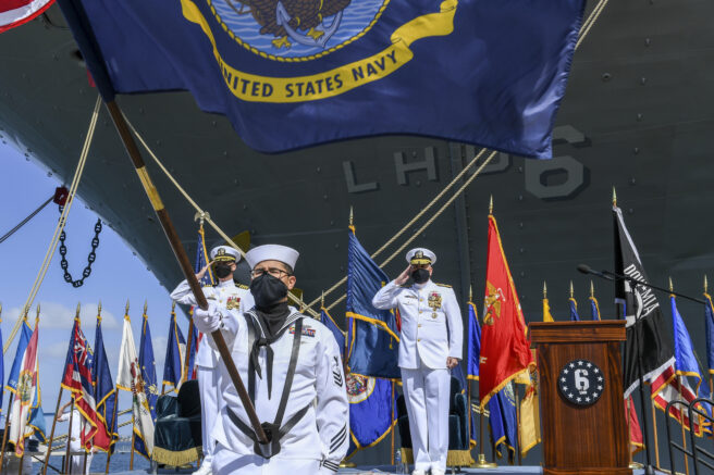 This photo provided by the U.S. Navy shows Rear Adm. Philip Sobeck, Commander, Expeditionary Strike Group Three, and Capt. G. S. Thoroman, commanding officer, amphibious assault ship USS Bonhomme Richard, salute the ensign for colors during a decommissioning ceremony at Naval Base San Diego April 14, 2021. The U.S. Navy has decommissioned the USS Bonhomme Richard docked off San Diego nine months after flames engulfed it in one of the worst U.S. warship fires outside of combat in recent memory. The ceremony Wednesday at Naval Base San Diego was not public with the Navy citing concerns over the spread of the coronavirus. (Mass Communication Specialist 2nd Class Alex Millar/U.S. Navy via AP)