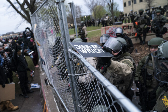 """A law enforcement officer tosses a demonstrator's sign that reads """"Justice for Wright"""" back over a perimeter fence during a protest over Sunday's fatal shooting of Daunte Wright during a traffic stop, outside the Brooklyn Center Police Department on Wednesday, April 14, 2021, in Brooklyn Center, Minn. (AP Photo/John Minchillo)"""