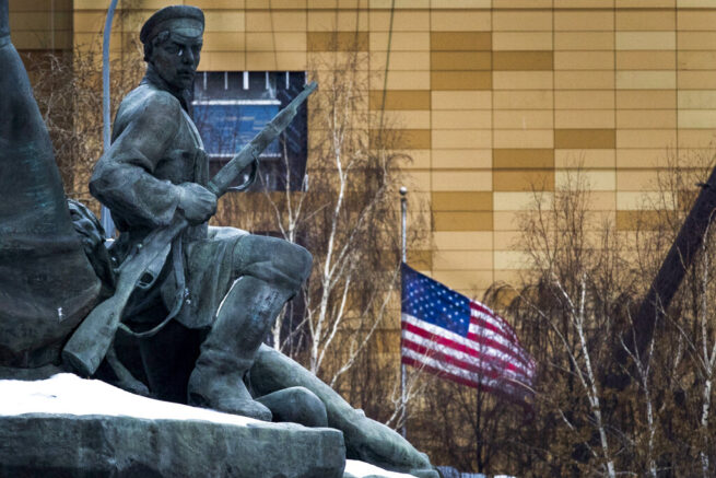 FILE - In this file photo taken on Friday, Dec. 30, 2016, The U.S. Embassy with its national flag, seen behind a monument to the Workers of 1905 Revolution in Moscow, Russia. Russian Foreign Minister Sergey Lavrov says Moscow will order 10 U.S. diplomats to leave Russia in a retaliatory response to the U.S. sanctions. Lavrov also said Moscow will add eight U.S. officials to its sanctions list and move to restrict and stop the activities of U.S. nongovernmental organizations from