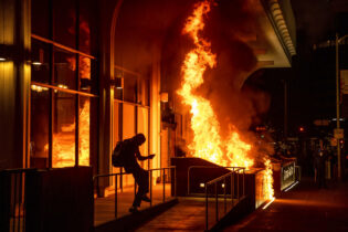 Demonstrators set fire to the front of the California Bank and Trust building during a protest against police brutality in Oakland, Calif., Friday, April 16, 2021. (AP Photo/Ethan Swope)