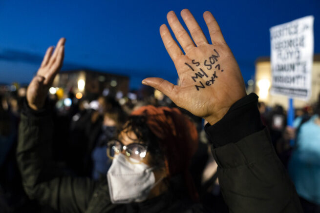 A demonstrator's hands are raised, one with a message, as law enforcement officers are stationed behind a perimeter security fence, during a protest over the fatal shooting of Daunte Wright by a police officer during a traffic stop, Saturday, April 17, 2021, in Brooklyn Center, Minn. (AP Photo/John Minchillo)