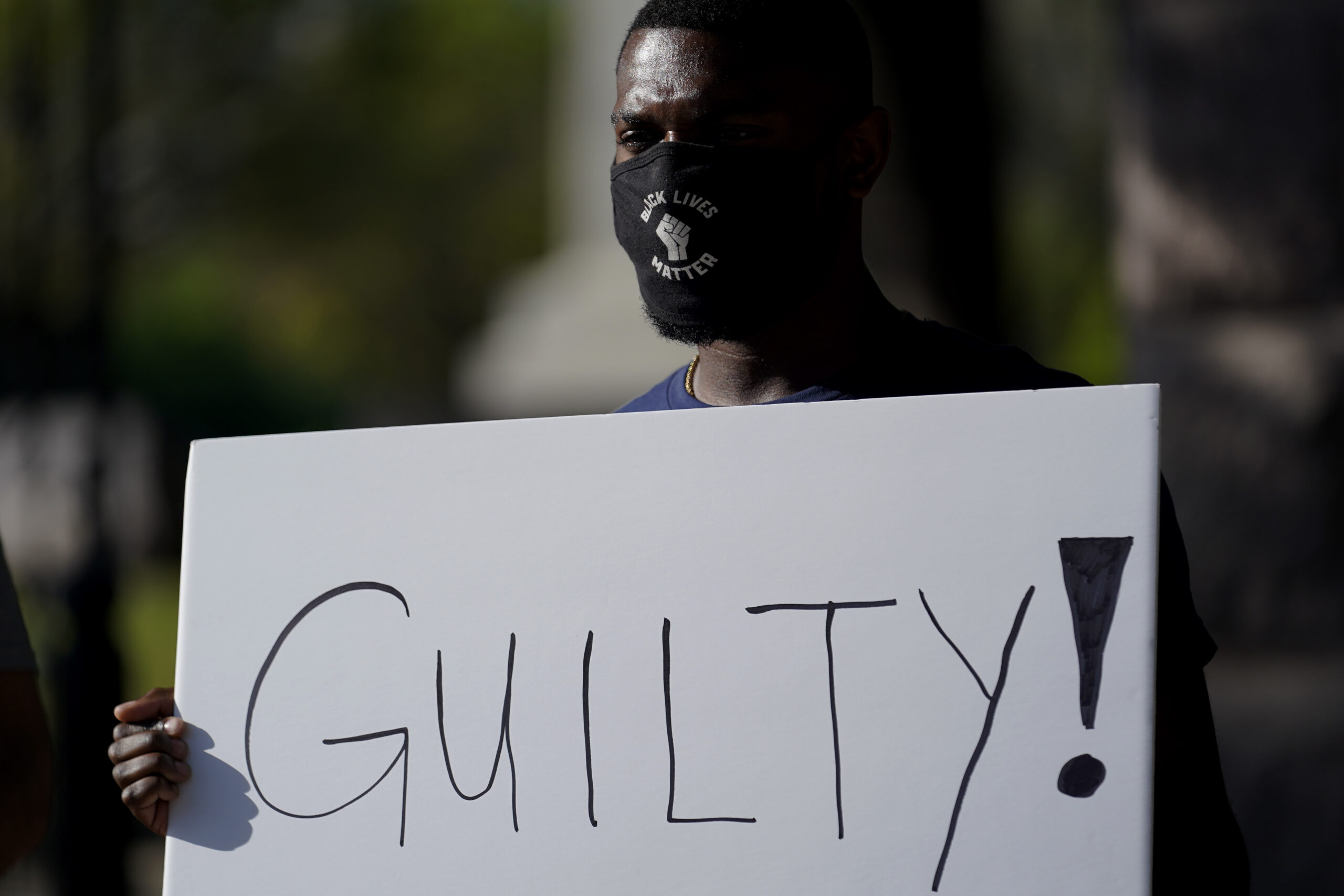 """Mike James stands with a sign reading """"Guilty"""" at the Texas Capitol, Tuesday, April 20, 2021, in Austin, Texas, after the guilty verdict in the murder trial of former Minneapolis police Officer Derek Chauvin was announced in the death of George Floyd. (AP Photo/Eric Gay)"""