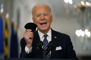 FILE - In this March 11, 2021, file photo, President Joe Biden holds up his face mask as he speaks about the COVID-19 pandemic during a prime-time address from the East Room of the White House in Washington. The U.S. is meeting President Joe Biden's latest vaccine goal of administering 200 million COVID-19 shots in his first 100 days in office, as the White House steps up its efforts to inoculate the rest of the public. (AP Photo/Andrew Harnik, File)