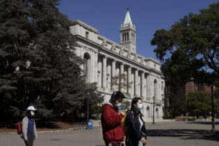 FILE - In this March 11, 2020, file photo, people wear masks while walking past Wheeler Hall on the University of California campus in Berkeley, Calif. Two of the nation's largest university systems say they intend to require COVID-19 vaccinations for all students, faculty and staff on University of California and California State University campuses this fall once the Food and Drug Administration gives formal approval, Thursday, April 22, 2021. (AP Photo/Jeff Chiu, File)
