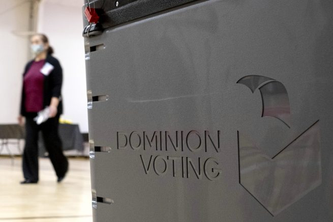 A worker passes a Dominion Voting ballot scanner while setting up a polling location at an elementary school in Gwinnett County, Ga., outside of Atlanta on Jan. 4, 2021. Newsmax has apologized to an employee of Dominion Voting Systems for airing false allegations that he manipulating voting machines or tallies on Election Day to the detriment of former President Donald Trump. Eric Coomer, security director for Dominion, subsequently dropped the conservative news network from a defamation lawsuit. (AP Photo/Ben Gray)