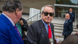 """LOS ANGELES, CA - DECEMBER 03: Attorneys L. Lin Wood (C) and Mark Stephen (L) speak to the media about their client, British rescue diver Vernon Unsworth (rear), as they arrive at US District Court on December 3, 2019 in Los Angeles, California. Unsworth is suing Tesla CEO Elon Musk for defamation over calling him """"Pedo Guy"""" and rapist. (Photo by Apu Gomes/Getty Images)"""