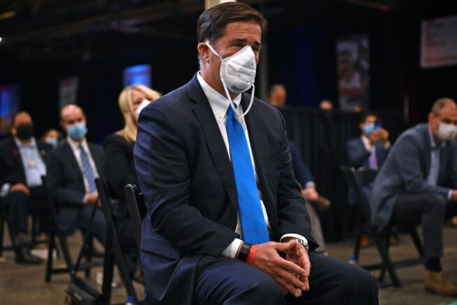 Arizona Governor Doug Ducey (C) listens as US President Donald Trump speaks during a tour of a Honeywell International plant that manufactures personal protective equipment in Phoenix, Arizona on May 5, 2020. (Photo by Brendan Smialowski / AFP) (Photo by BRENDAN SMIALOWSKI/AFP via Getty Images)
