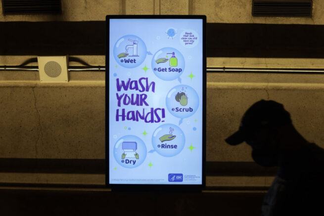 WASHINGTON, DC - APRIL 07: A CDC hand washing guideline is seen on a screen as a passenger passes by at Metro Center Station April 7, 2020 in Washington, DC. Washington Metropolitan Area Transit Authority announced that it is cutting late night service and closing all Metro stations at 9pm daily until further notice. (Photo by Alex Wong/Getty Images)